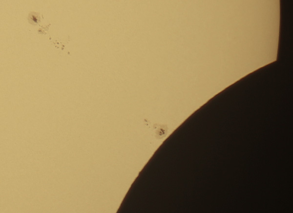 Crop showing sunspots and lunar mountains.